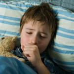 Sick boy in bed coughing with Teddy-bear