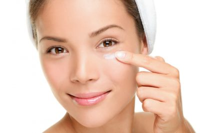 Face cream woman applying skin cream under eyes. Beauty eye contour cream, wrinkle cream or anti-aging skin care cream. Beautiful young mixed race Asian / Caucasian female beauty model in her 20s isolated on white background.